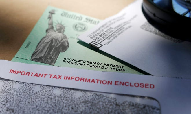 In this April 23 file photo, President Donald Trump's name is seen on a stimulus check issued by the IRS to help combat the adverse economic effects of the COVID-19 outbreak.
