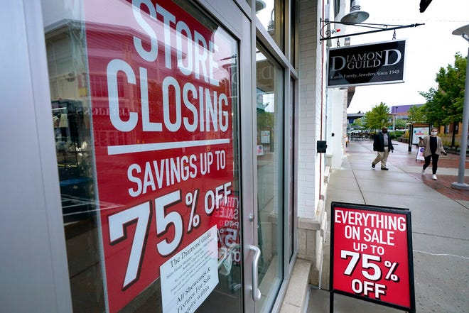 In this Wednesday, Sept. 2, 2020, file photo, passers-by walk past a business storefront with store closing and sale signs in Dedham, Mass. U.S. employers advertised for slightly fewer jobs in August while their hiring ticked up modestly. The Labor Department said Tuesday, Oct. 6, 2020,  that the number of U.S. job postings on the last day of August dipped to 6.49 million, down from 6.70 million July.