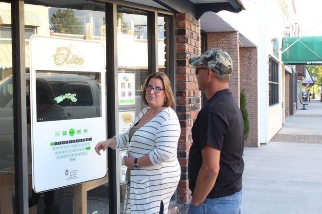 Realtor Sandra Haugen demonstrates the new interactive system in the window of Elite Real Estate Management on Mt. Shasta Boulevard.