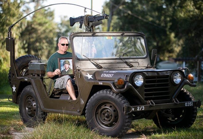 Paul Hart holds a portrait of his uncle Ronald Robert Ozimek, who was killed in Vietnam at the age of 19 in October 1969. He has dedicated his 1970 Ford M151A2 MUTT, which was used in Vietnam, to his late uncle.