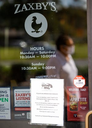 A patron walks past the entrance of the Zaxby's at 3019 SE Maricamp Road on Thursday. A notice on the door refers to the Ocala City Council's emergency mask ordinance enacted in August. The ordinance will expire on Oct. 24. The council will revisit the issue on Tuesday for a possible extension.