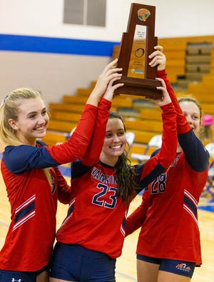 Vanguard's (9) Emma Ehmann, (23) Adyla Kerley and (28) Sophie Reed hold up the district trophy after defeating the Lake Weir Hurricanes in three straight sets, 25-7, 25-9, 25-23 in the District 5-5A volleyball finals.