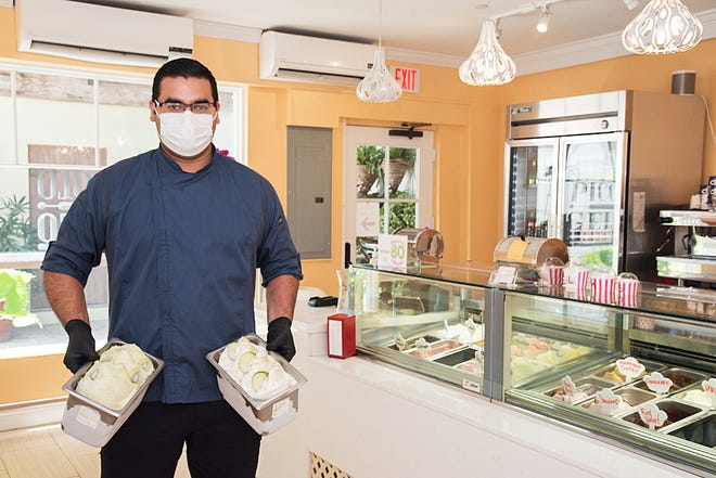 Gelato-maker Victor Corrales holds some recent flavors he has developed. His newest include pumpkin-flavored gelatos.