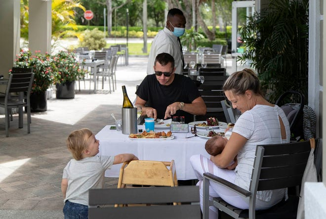 Declan Orpen, with his wife Cassandra, son, Oliver, 20 months, and new born daughter Addison were the first to order dine-in lunch at Oli's Fashion Cuisine when it reopened following the coronavirus outbreak in May. States have tried shutting down bars and limiting restaurants to outdoor seating to slow the coronavirus's spread. [ALLEN EYESTONE/palmbeachpost.com]