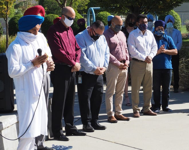 """A """"Call for Justice"""" gathering Thursday in the name of murder victim Parmjit Singh at Tracy's Gretchen Talley Park opened with a Sikh prayer. Among those present are Tracy Mayor Robert Rickman, third from left, and San Joaquin County Supervisor Miguel Villapudua, fourth from left."""