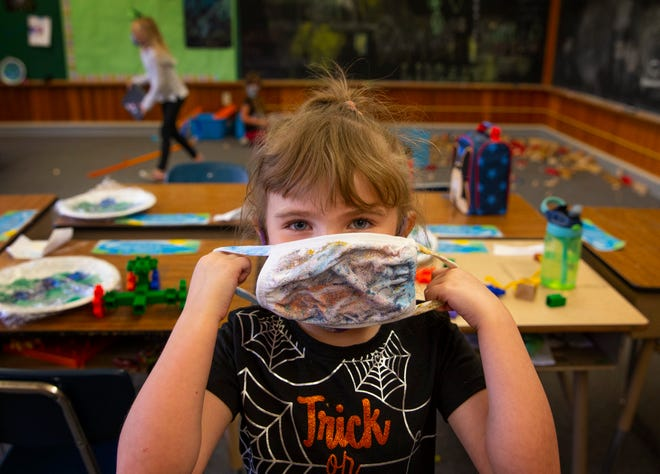 Five-year-old Avienda Scott models a face mask she made at the old Latham School in Cottage Grove. The Eugene Family YMCA created the youth program in the South Lane School District through a partnership with the Ford Family Foundation and the Pacific Power Foundation.