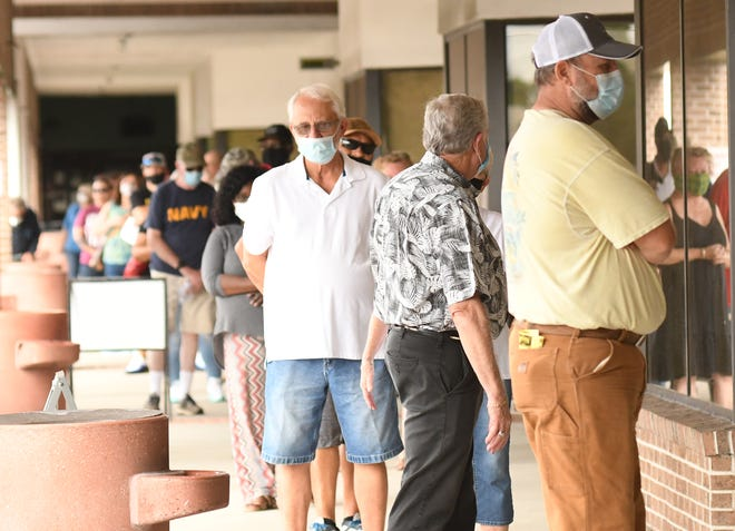People wait in line at the New Hanover County Government Center to cast their vote as thousands of voters came out Thursday Oct. 15, 2020 for early voting ahead of this year's general election during the one-stop early voting period.  One stop voting allows residents to register to vote and cast a ballot on the same day. County residents can also use one stop voting to update the name or address on their registration, if needed.  From Oct. 15 to Oct. 31, New Hanover voters will have nine early-voting locations to choose from to cast their ballots.  [KEN BLEVINS/STARNEWS]