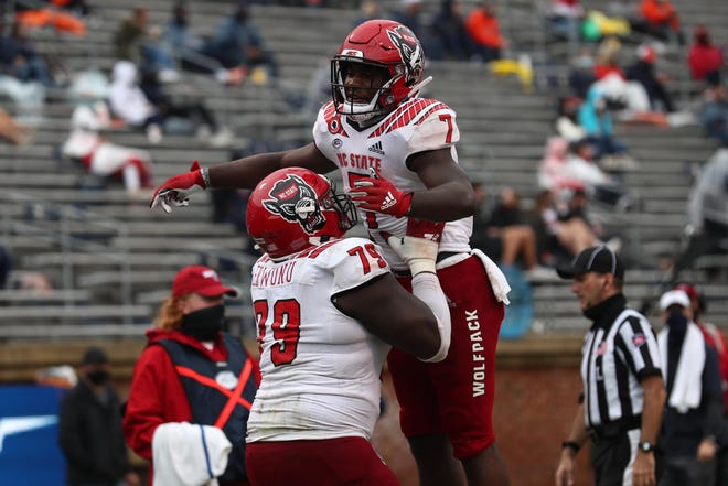 "NC State's Zonovan Knight (7) celebrates with teammate Ikem Ekwonu after scoring a touchdown in Saturday's 38-21 win over Virginia. Knight has 13 of the Pack's 40 ""explosion"" plays, which account for more than 10 yards, this season."