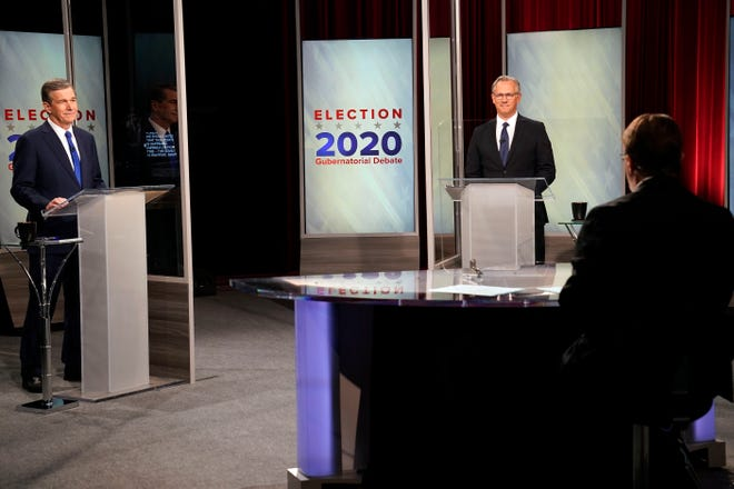 North Carolina Gov. Roy Cooper, left, and Lt. Gov. Dan Forest participate in a live televised debate moderated by Wes Goforth at UNC-TV studios in Research Triangle Park, N.C., Wednesday, Oct. 14, 2020. (AP Photo/Gerry Broome)