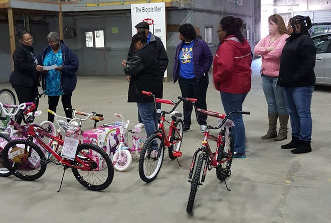 People gather for the annual bike giveaway, which was started by Moses Mathis.