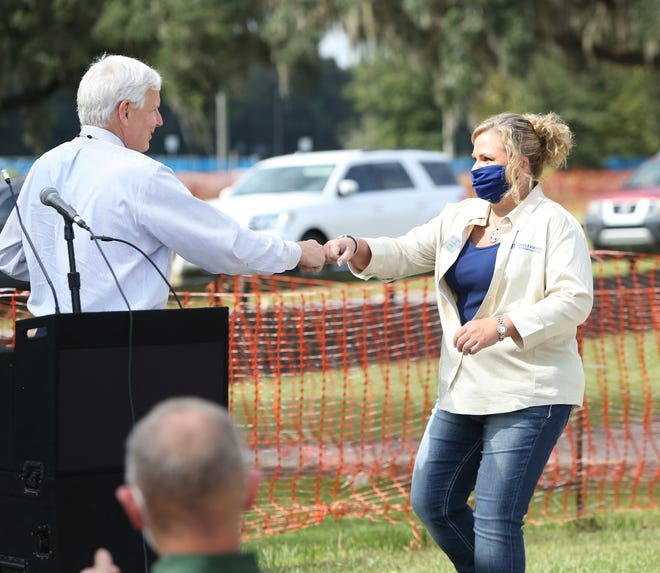 Scott Angle, left, the new vice president of UF/IFAS, fist bumps Cynthia Sanders, director of the UF/IFAS Alachua County Extension, as she comes to speak during the groundbreaking ceremony for the new extension office at the site of the old Canterbury Equestrian Showplace in Newberry. The facility will take about a year to finish, but will be a new long-term home for the extension office and fairgrounds.