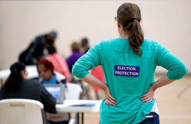 A poll watcher observes voters in Nashville, Tenn., in 2016.