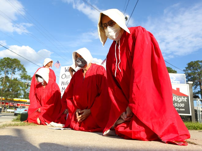 """A group of women dressed in red robes in reference to Margaret Atwood's """"The Handmaid's Tale,"""" protest against the government making laws to regulate men's and women's bodies, in Melrose, Fla., on Oct. 15, 2020."""