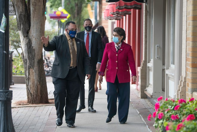 Administrator Jovita Carranza, head of the U.S. Small Business Administration, is led down Union Avenue by Steven Trujillo, president/CEO of the Latino Chamber of Commerce.
