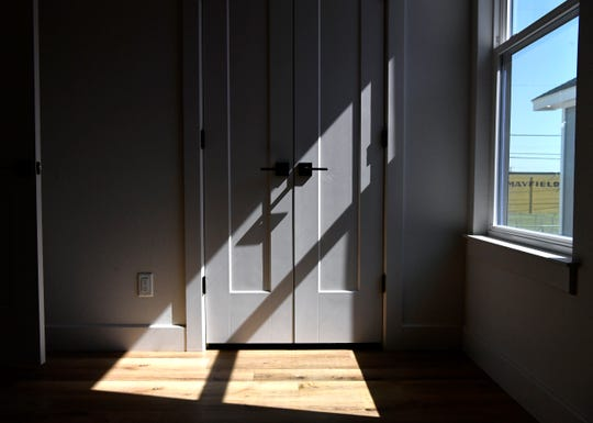 Light streams into a bedroom while the Mayfield Paper Company building can be seen through the window in one of the five houses in the Quarters on Pecan Street development. The new homes in the SoDA District were built on the site of a former warehouse covered in corrugated tin.