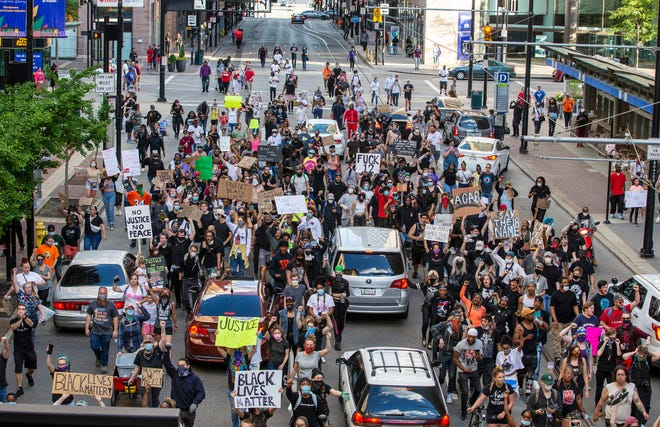 Protesters march north on Walnut during the second day of protests Saturday, May 30, 2020, through downtown Cincinnati.