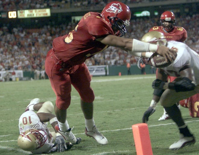 Seneca Wallace gets within inches of the end zone before being stopped by Florida State's Jerome Carter with four seconds left in a 2002 game. Rodney White/Register file photo - -Register photo by Rodney White -- 8.24.02