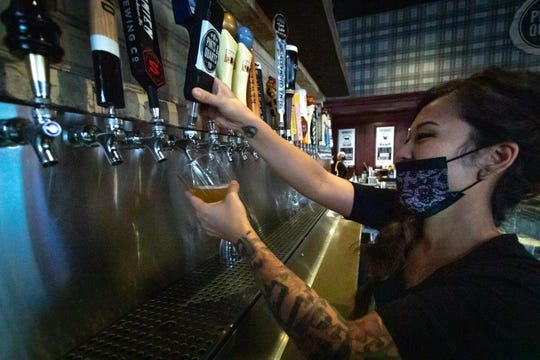 Bartender Hana Lorenz of Whitehall pours a beer at Pints and Quarts restaurant in the Muskegon area.