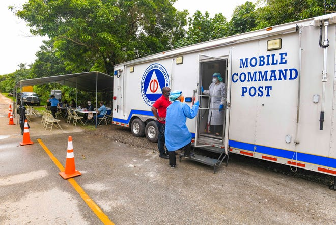 Health care workers process samples inside a Guam Homeland Security/Office of Civil Defense mobile command post in Yigo, in this Oct. 15 file photo.