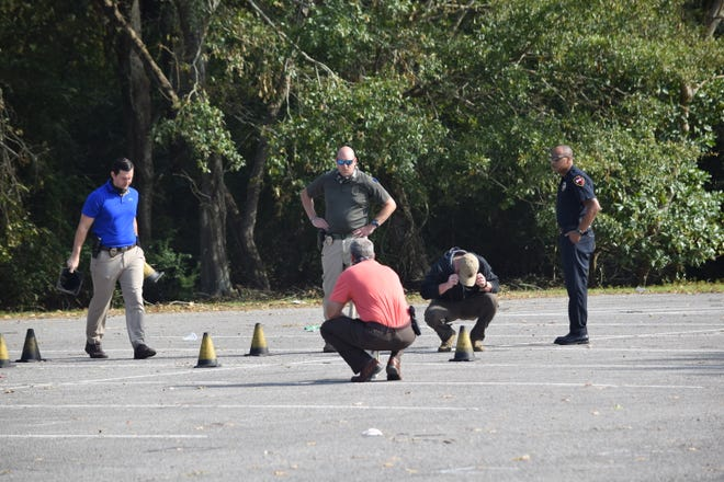 Lafayette Police detectives use cones to mark shell casings from a gun in a parking lot at Moore Park in Lafayette, Louisiana, on Oct. 15, 2020, hours after a shooting at a large party left two dead and two injured.