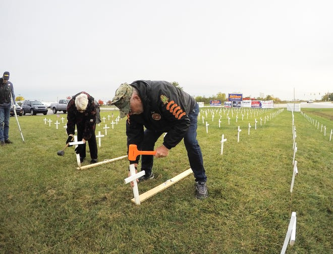 American Legion Auxiliary member Pat Washburn, at left, and Marine Corps League and American Legion member Ron Brooks were among a group of volunteers planting crosses in front of the American Legion Devereaux Post 141 at Grand River and Highland Road Wednesday, Oct. 14, 2020.