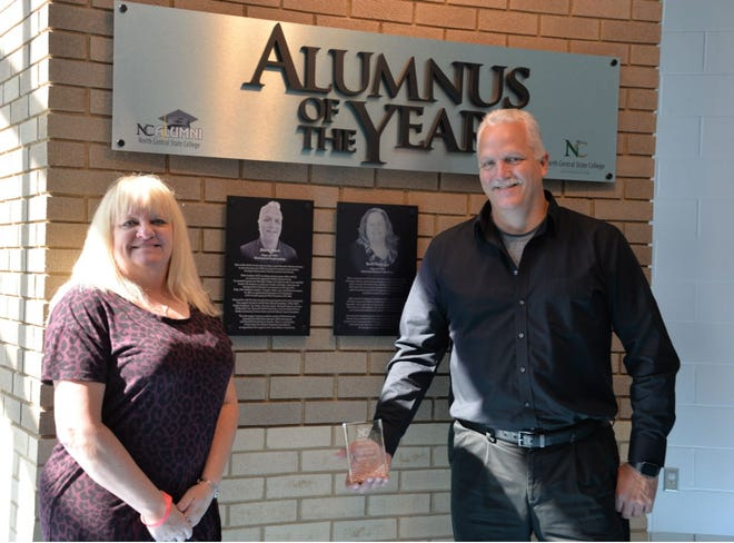 Mark Hess and his wife, Pam, pose near the Alumnus of the Year display at NCSC.