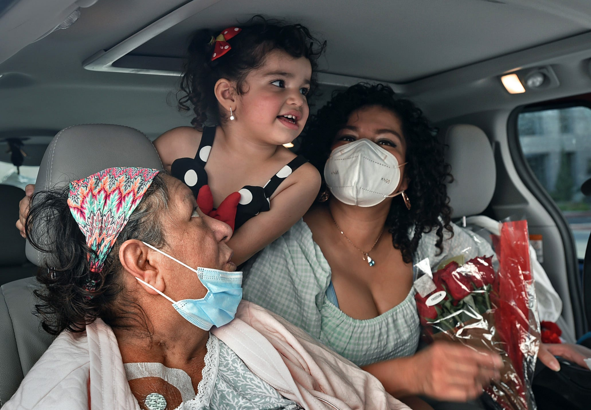 Patricia Villaseca sits in the family car with granddaughter Gadi Camacho, 4, and daughter Cyndi Camacho after being discharged from Saint Mary's Regional Medical Center where she was hospitalized 5 months after contracting COVID-19 in April 2020. Villaseca, 60, survived COVID-19 despite having an underlying condition. Her daughter Cyndi Camacho, right, also contracted COVID-19 while being pregnant.