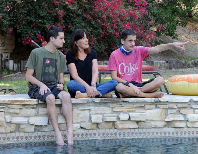 Travis Hernandez, 30, left, his mother Doreen Salz and his brother Evan Hernandez, 27, right, hang out at their pool. Salz stands to lose more than $500 a month in her pension under a California Supreme Court decision.