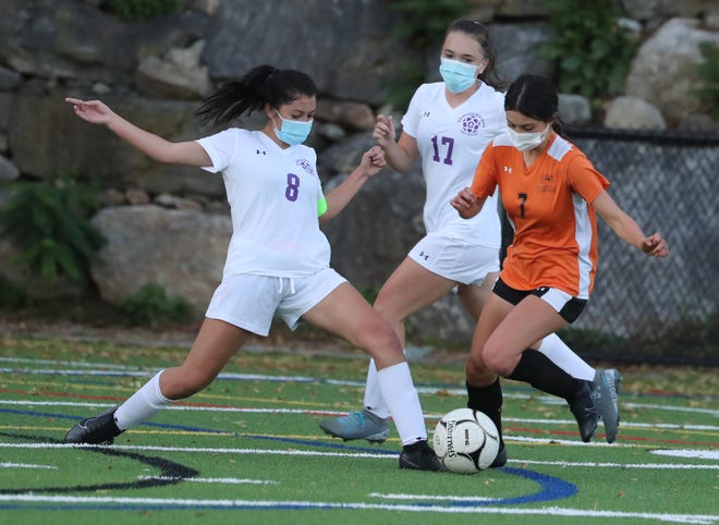 Mamaroneck's Jessica Bowman (7, right) tries to work past the New Rochelle defense during the Tigers' 3-1 win over the Huguenots on Oct. 14, 2020.