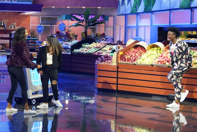 "Host Leslie Jones, right, is having a good time as she engages with contestants on ABC's revival of ""Supermarket Sweep."""