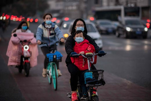 People wearing face masks as a preventive measure against the Covid-19 coronavirus commute during rush hour in Beijing on October 15, 2020.