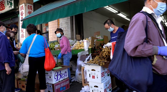 People walk and shop at the produce market in Chinatown in downtown San Francisco on Sept. 29, 2020.