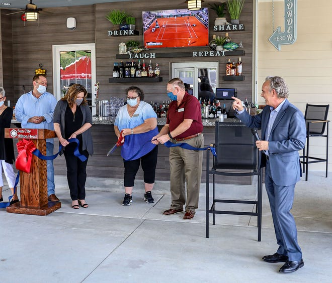 Sun City board of directors members cut the ribbon at the new AL's Pub and Pizzeria at Argent Lakes.