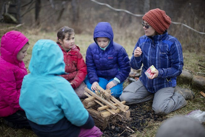 Christin Butler, Director of Education at Solid Ground School, works with some of the older girls on starting a fire and the scientific principals involved during a January class. The students typically spend 25 to 30%of the day outdoors, regardless of the weather, but due to COVID-19 they moved classes entirely outdoors.