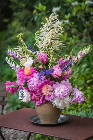 Peonies and other spring flowers create a lush arrangement.