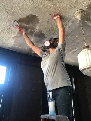 When removing a popcorn ceiling, hold a flat-edged metal scraper to the ceiling at an angle and gently slide the popcorn texture off. Use a putty knife to tackle hard-to-reach edges.