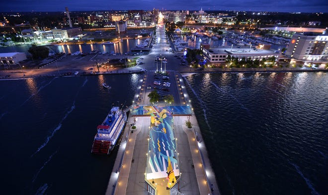 """The mural """"Flotsam"""" is seen on the second-floor observation deck at Dobbins Landing, bottom center, at dusk near the Bicentennial Tower in Erie on Sept. 4, 2019. International artist Rafael Gerlach, known as SatOne, painted the mural."""