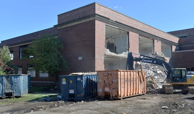 A northwest wall is taken down at the former Roosevelt Middle School as demolition continues on Friday in Erie.