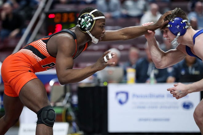 Cathedral Prep's Paniro Johnson, left, places his hand on the forehead of Connellsville's Jared Keslar during the 145-pound third-place match during the PIAA Class 3A championships, held March 7, 2020, at Giant Center in Hershey, Pennsylvania.