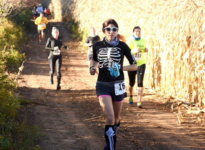 A runner leads a pack past the corn maze at Pumpkin Junction in Sauquoit during the Utica RoadRunners' 13th 5K Skeleton Run Sunday, Oct. 11, 2020.
