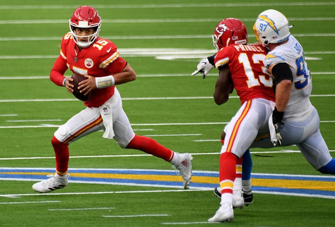 Quarterback Patrick Mahomes, left, of the Kansas City Chiefs scrambles in a game against the Los Angeles Chargers earlier this season. Mahomes and the high-scoring Chiefs offense faces a high-scoring Buffalo Bills offense in what could be a shootout Monday in Buffalo.