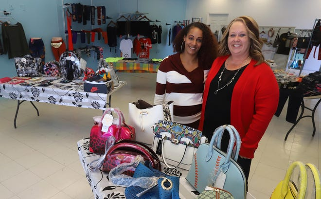 Longtime Burlington friends Stacy Morse and Susan Swore show off items in their store Purseuasive Pieces Friday at 3200 Division St. in Burlington. The shop carries a variety of items for women, children and men.
