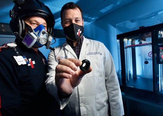 Tony Hayes (left), program manager of TraumaOne flight services, wears a respirator modified with a 3D-printed filter adapter that radiologist Travis Meyer is holding at UF Health in Jacksonville. Meyer, the director of the 3D print lab, used the printer at right to make the adapter while other equivalents were on backorder.