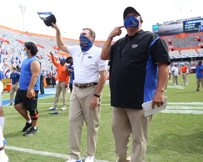 Universty of Florida football coach Dan Mullen (L) and defensive coordinator Todd Grantham, seen here celebrating a win over South Carolina, know getting through a full schedule in the 2020 season is more tenuous than ever. [Brad McClenny/The Gainesville Sun]