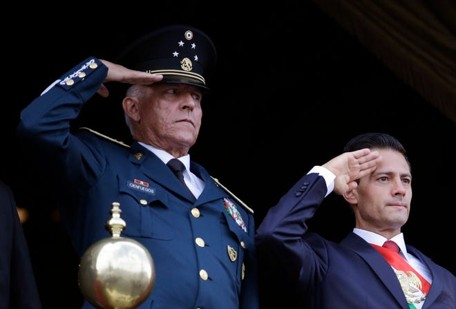 Defense Secretary Gen. Salvador Cienfuegos, left, and Mexico's President Enrique Pena Nieto, salute during the annual Independence Day military parade in Mexico City's main square in September 2016. Mexico's top diplomat said Cienfuegos, the country's former defense secretary, was arrested in Los Angeles. Foreign Relations Secretary Marcelo Ebrard wrote Thursday in his Twitter account that U.S. Ambassador Christopher Landau had informed him of Cienfuegos' arrest.
