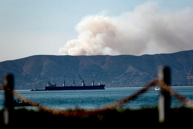 Seen from Alameda, Calif., a grass fire burns in South San Francisco on Friday. Portions of Northern California remain under red flag fire warnings due to high temperatures and dry winds.