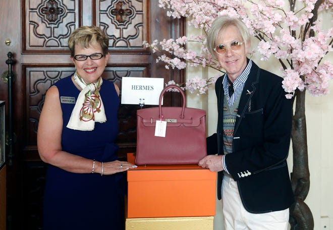 "Kathleen Guzman and Michael Tonello stand next to a Birkin bag for auction at last season's Center for Family Services 21st Annual Old Bags Luncheon. Tonello, who's also known as the ""Birkin Houdini"" was the event's keynote speaker."