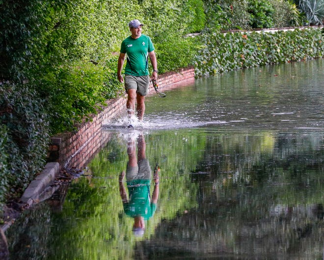 Shane Gallagher, of West Palm Beach, joyfully splashes his way along the flooded Lake Trail during king tides.