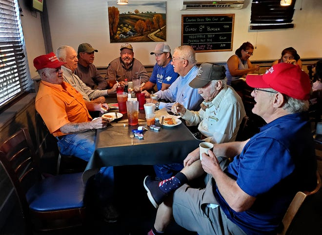 "In deep red country, the unofficial ""Liar's Club"" gathers at Glady's Restaurant in Okeechobee in the mornings. From right to left, Jim Craig, Gordy Peer, Dr. Randall Mims, Gregg Maynard, Elve Posey, Charlie Norris, Dowling Watford and Noel Chandler like to swap tall tales and enjoy warm biscuits slathered in thick gravy.  Chandler is not so different from the group he cuts up with, and the banter is sidesplitting even when it turns to serious topics like politics."