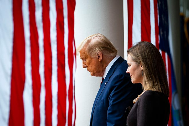 FILE - President Donald Trump walks with Judge Amy Coney Barrett prior to announcing Coney as his pick to be the next Supreme Court. [Al Drago/The New York Times]